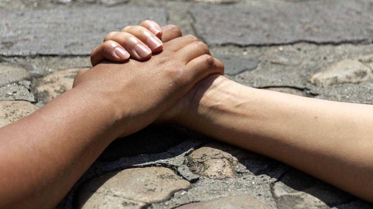 Zwei Arme auf einem Steinboden, eine dunkelhäutiger und einer hellhäutigen Person, die sich an den Händen halten.