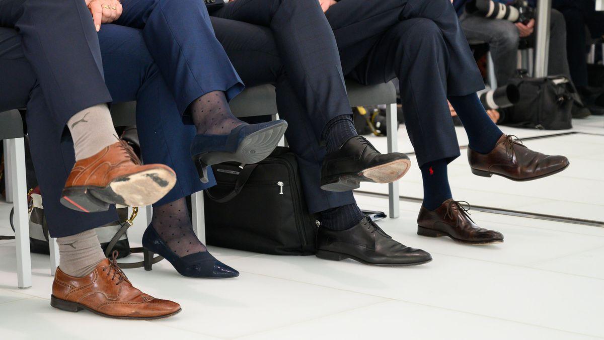Männer und Frauen sitzen während einer Pressekonferenz nebeneinander.
