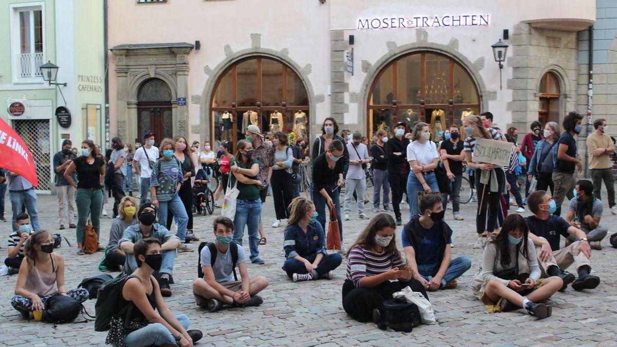 Menschen bei einer Kundgebung vor dem Regensburger Rathaus