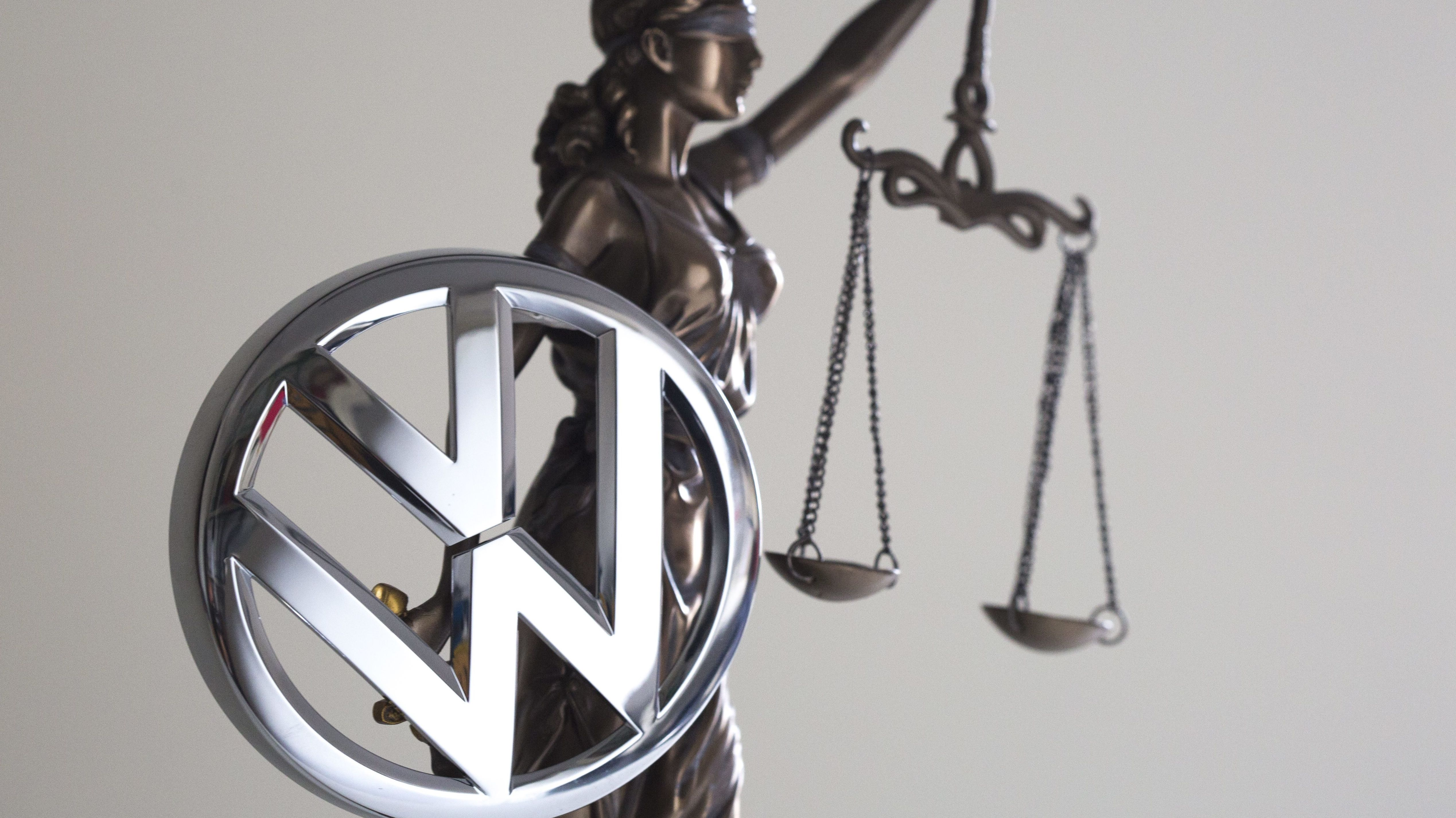 Eine Statue der Justitia neben einem VW-Logo.