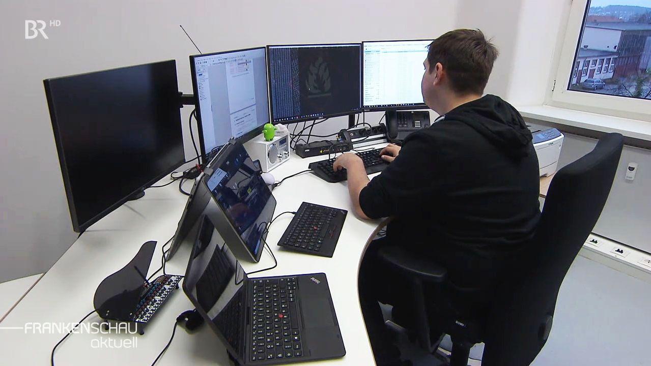 Ein Mann sitzt vor mehrere Computerbildschirmen.