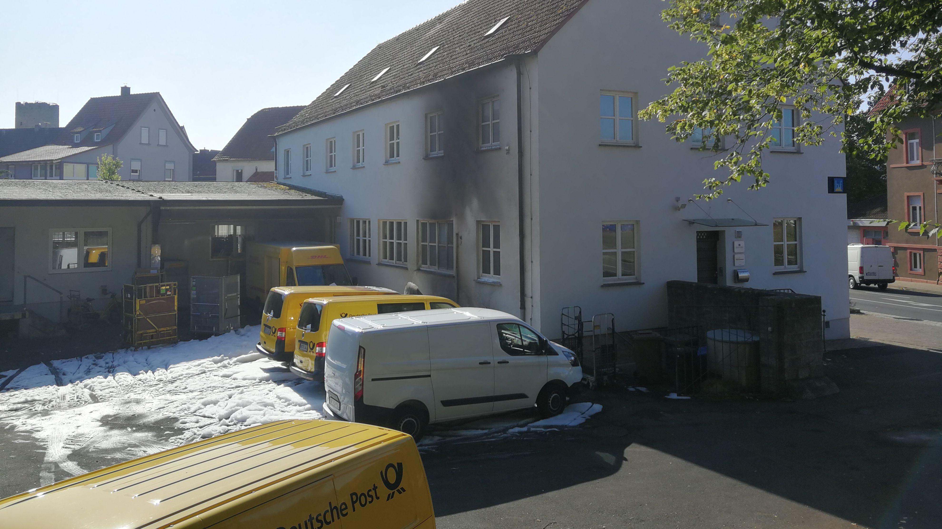 In einem Hinterhof stehen mehrere Fahrzeuge der Post. An einem Gebäude sind Spuren von Ruß zu sehen.