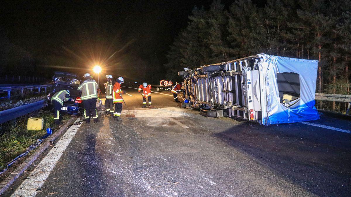 Ein umgekippter Lastwagen liegt auf der A70, daneben räumen Einsatzkräfte die Unfallstelle.