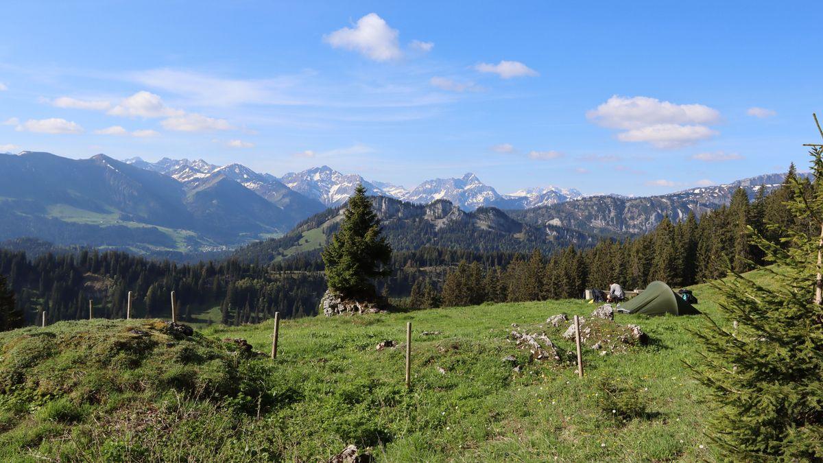 Zelt auf einer Wiese, im Hintergrund Berge