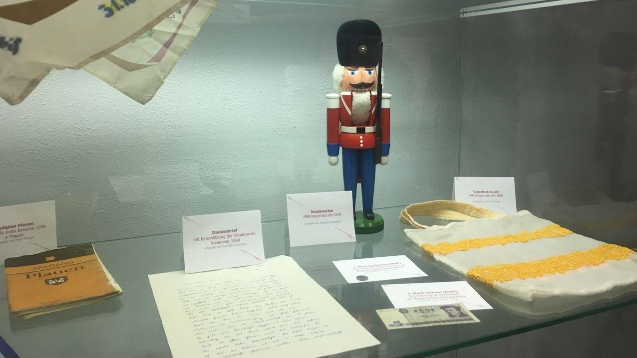 Ein Nussknacker steht in einer Glasvitrine.Davor liegen Dokumente und ein Stoffbeutel.