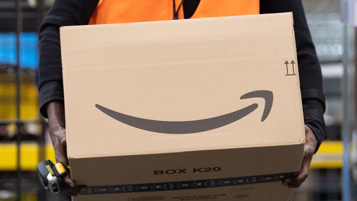 Ein Sortiermitarbeiter von Amazon trägt in einem Verzeilzentrum ein Paket
