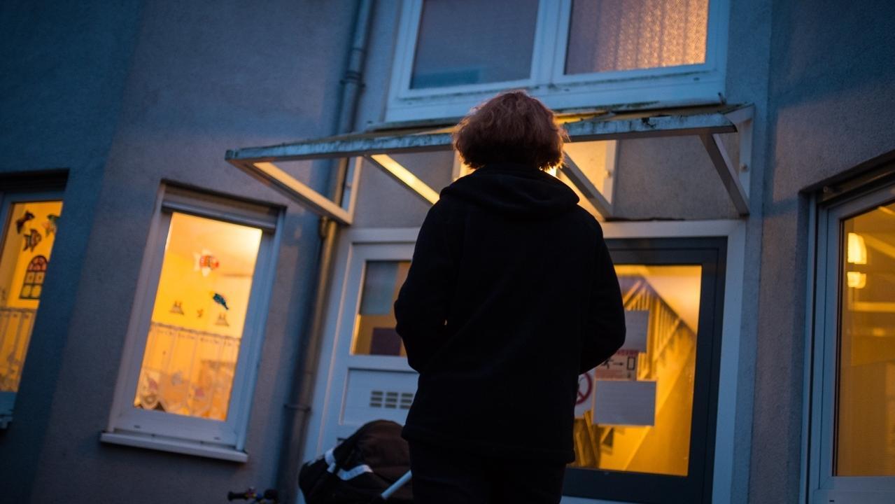 Eine Frau steht vor einem Frauenhaus.