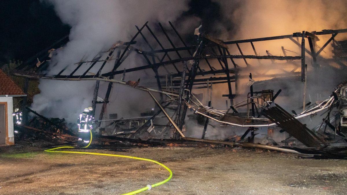 Feuerwehrleute vor der völlig zerstörten Halle.