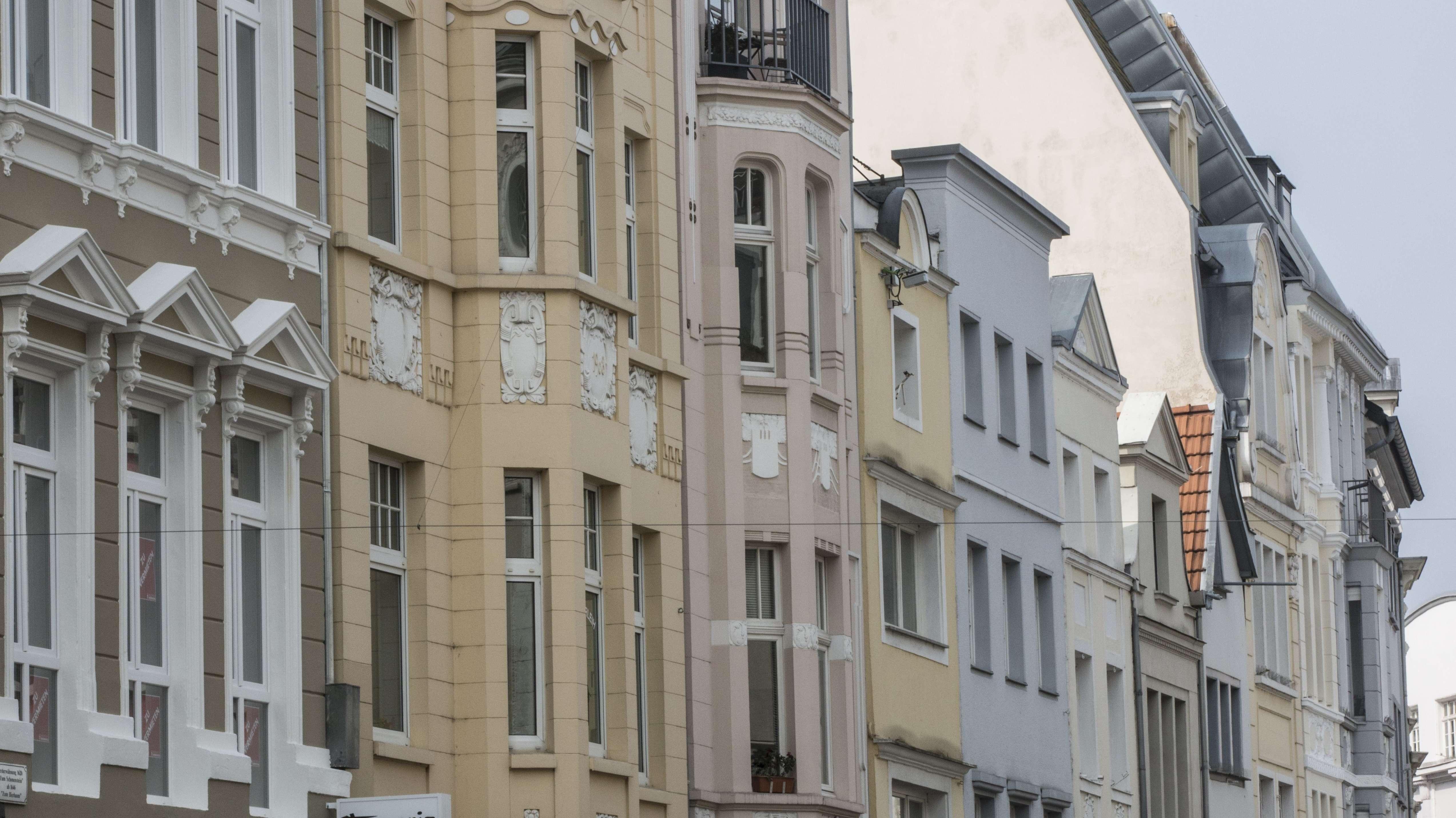 Eine Häuserzeile mit verschiedenen Wohnungen entlang einer Straße.