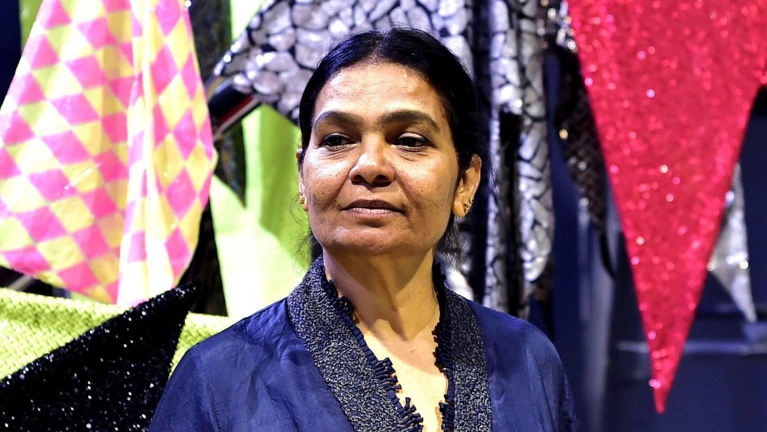 Die indische Künstlerin Sheela Gowda steht im Pirelli Hangar Bicocca vor einer Reihe bunter Fahnen