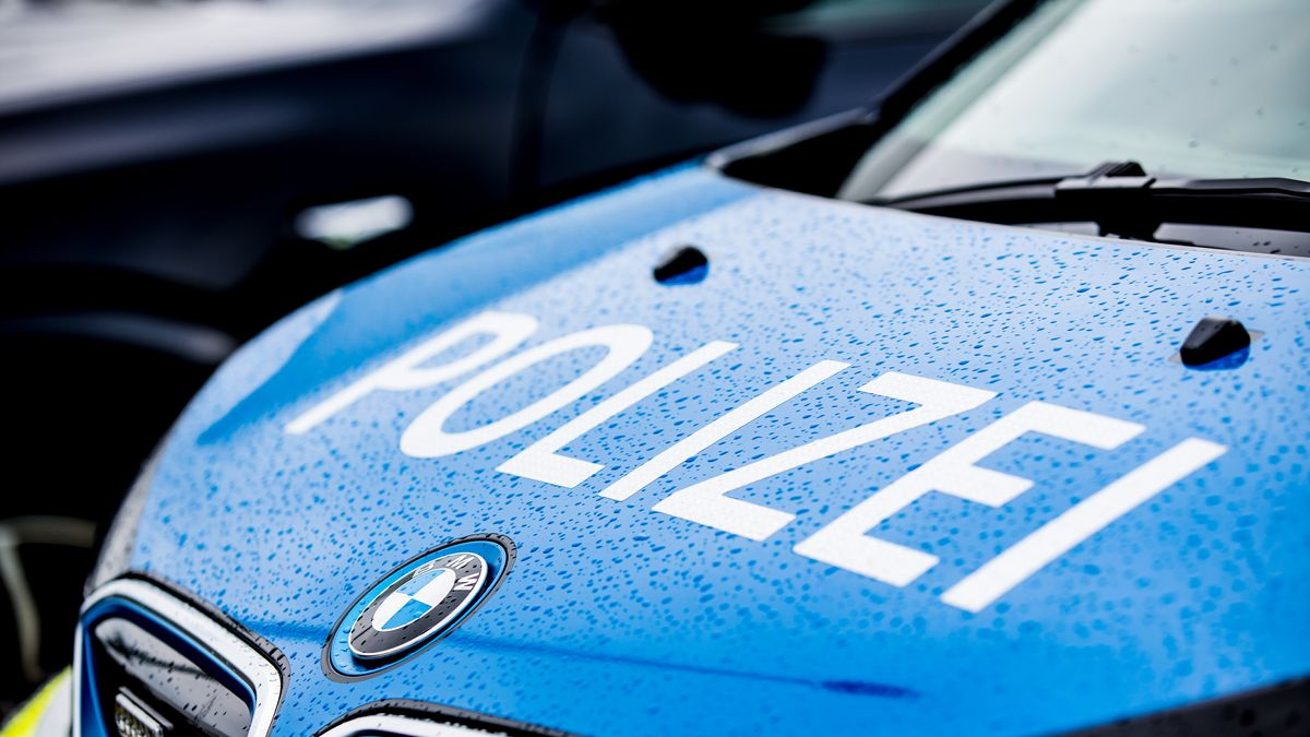 Polizeiauto  mit Aufschrift im Regen