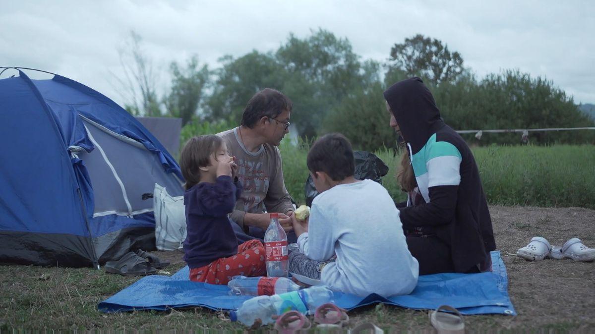Hassan Gholam sitzt mit seiner Familie auf einer Decke und isst gemeinsam vor einem Zelt.
