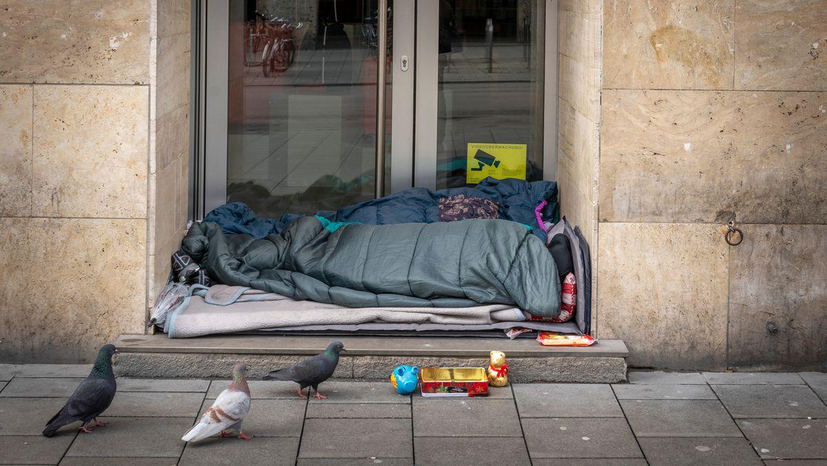 Zwei Menschen liegen in Schlafsäcken gehüllt in einem Hauseingang. Vor ihnen eine Box für Spenden. Drei Tauben gehen vor ihnen auf und ab.