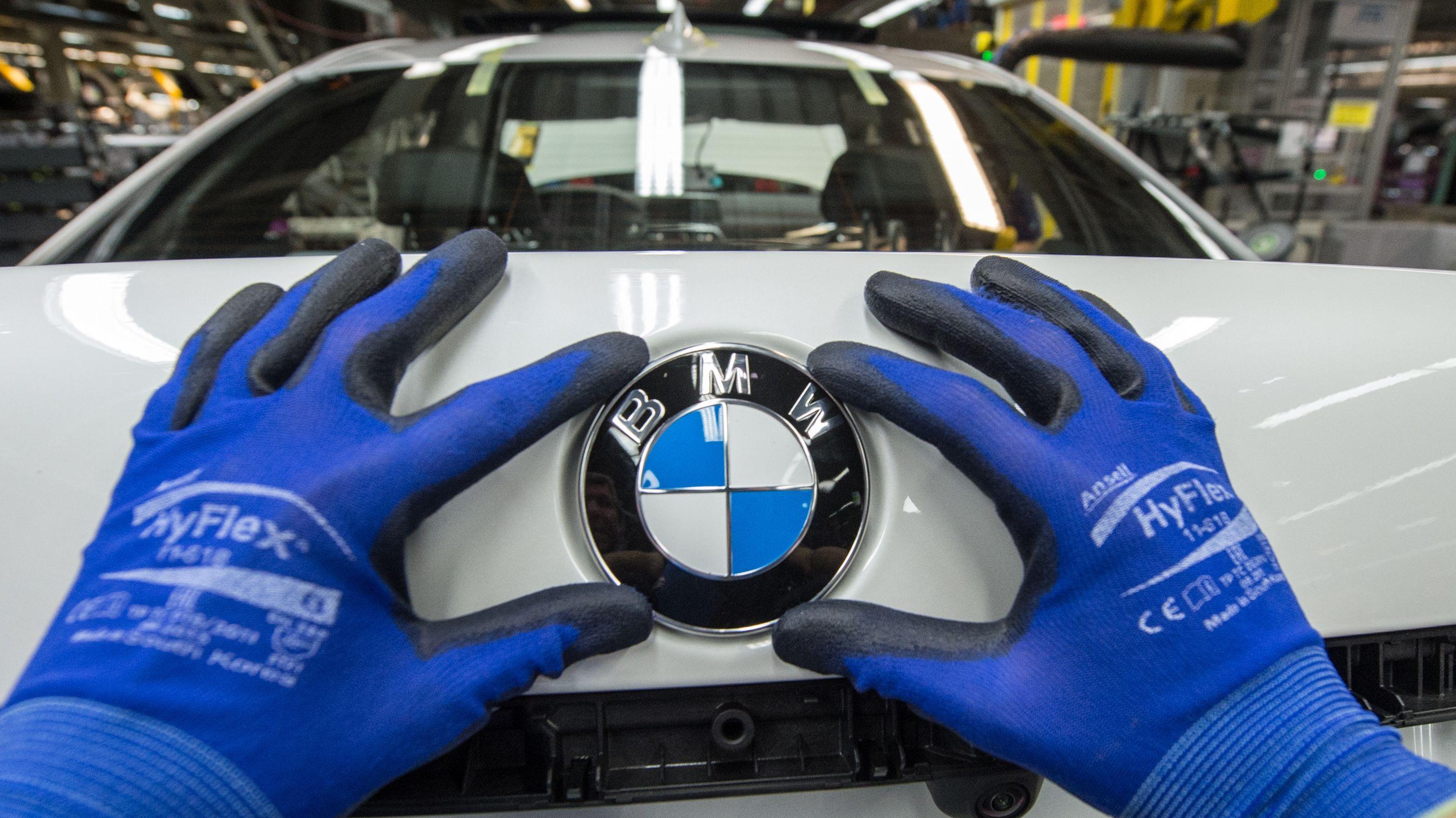Ein Mitarbeiter montiert im BMW-Werk Dingolfing ein BMW-Emblem auf den Kofferraumdeckel eines Fahrzeugs