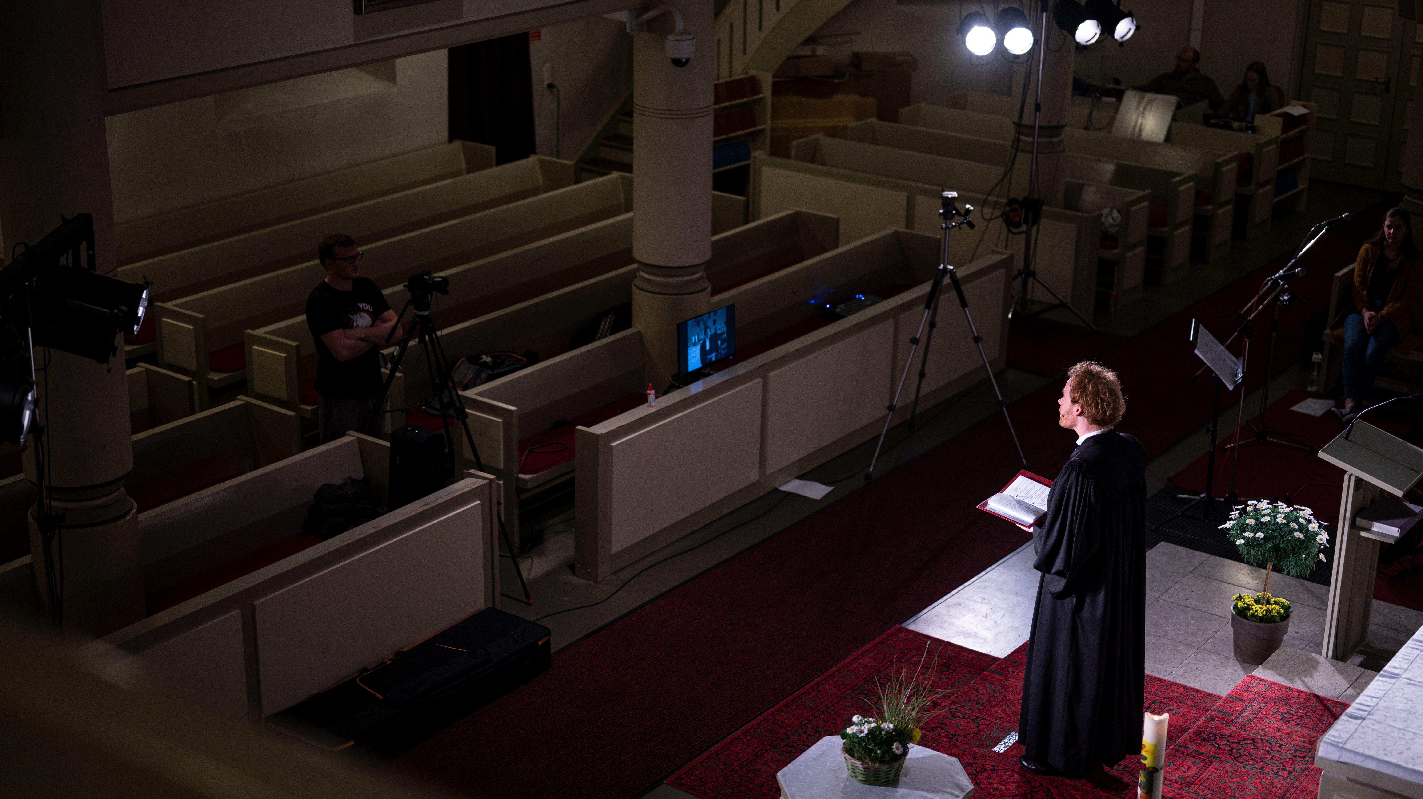 Pfarrer hält einen Gottesdienst vor einer Kamera in einer leeren Kirche.