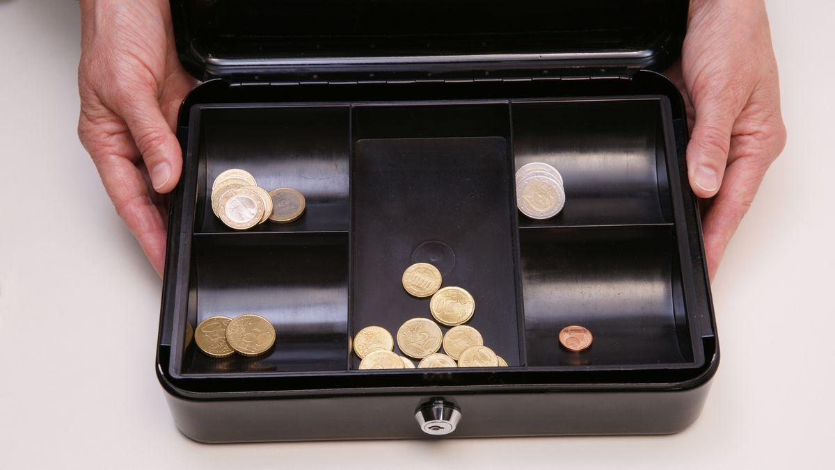 Zwei Hände halten eine schwarze Geldkassette mit Euromünzen.