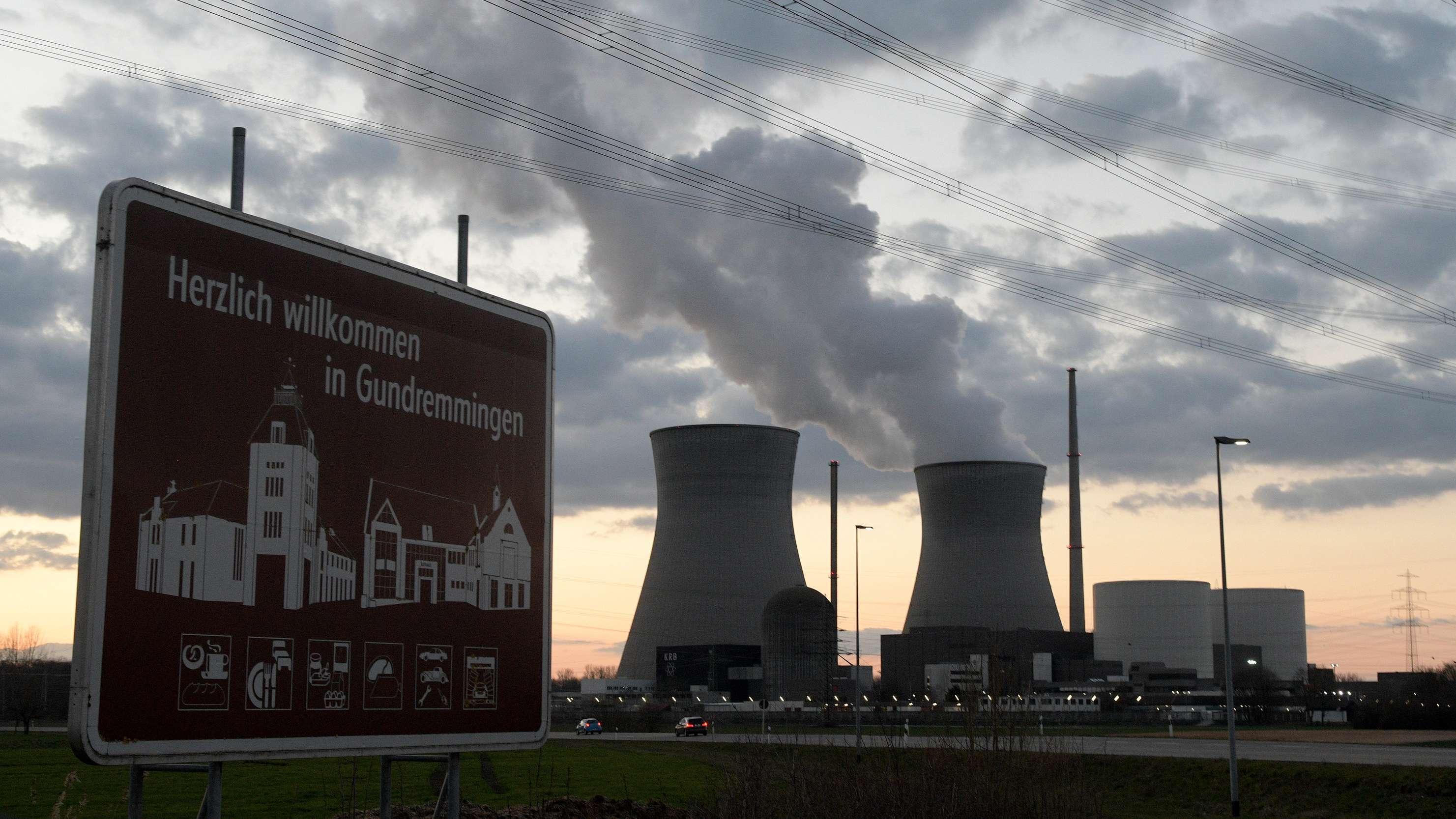 """Das Atomkraftwerk Gundremmingen und ein """"Herzlich willkommen in Gundremmingen""""-Schild in der Morgendämmerung."""