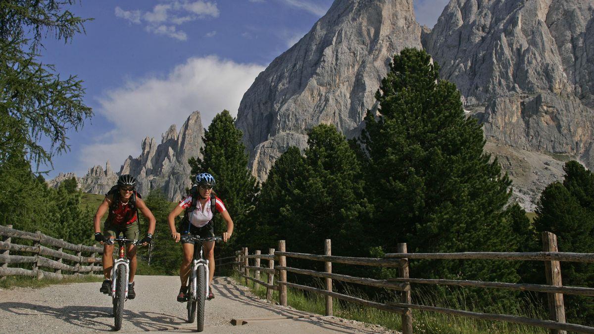 Zwei Radfahrerinnen vor dem Bergpanorama der Dolomiten.