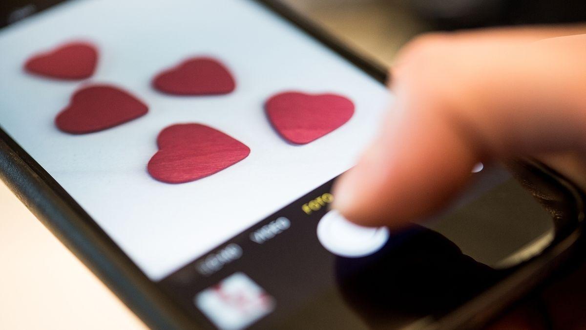 Eine Frau fotografiert mit einem Smartphone Herzen.