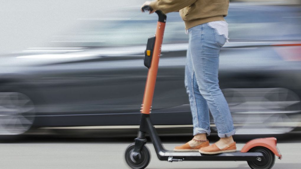 Ein Mensch fährt auf Elektroroller auf der Straße an einem Auto vorbei.
