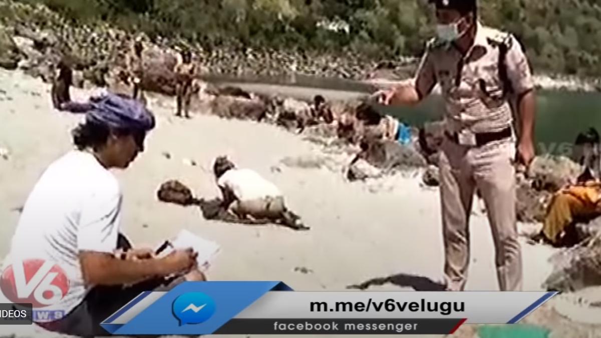 Ein Polizist überwacht, wie Urlauber am Ufer des Ganges Strafarbeiten schreiben