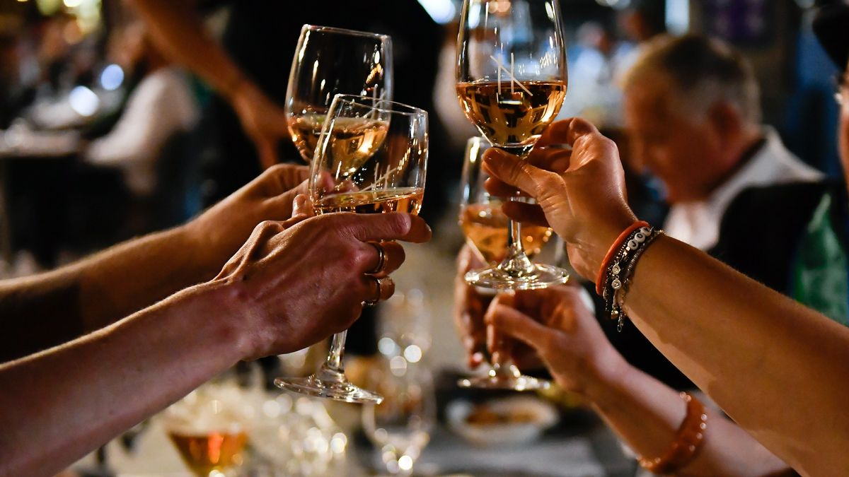 Mehrere Menschen stoßen in einem Restaurant mit Weingläsern an.