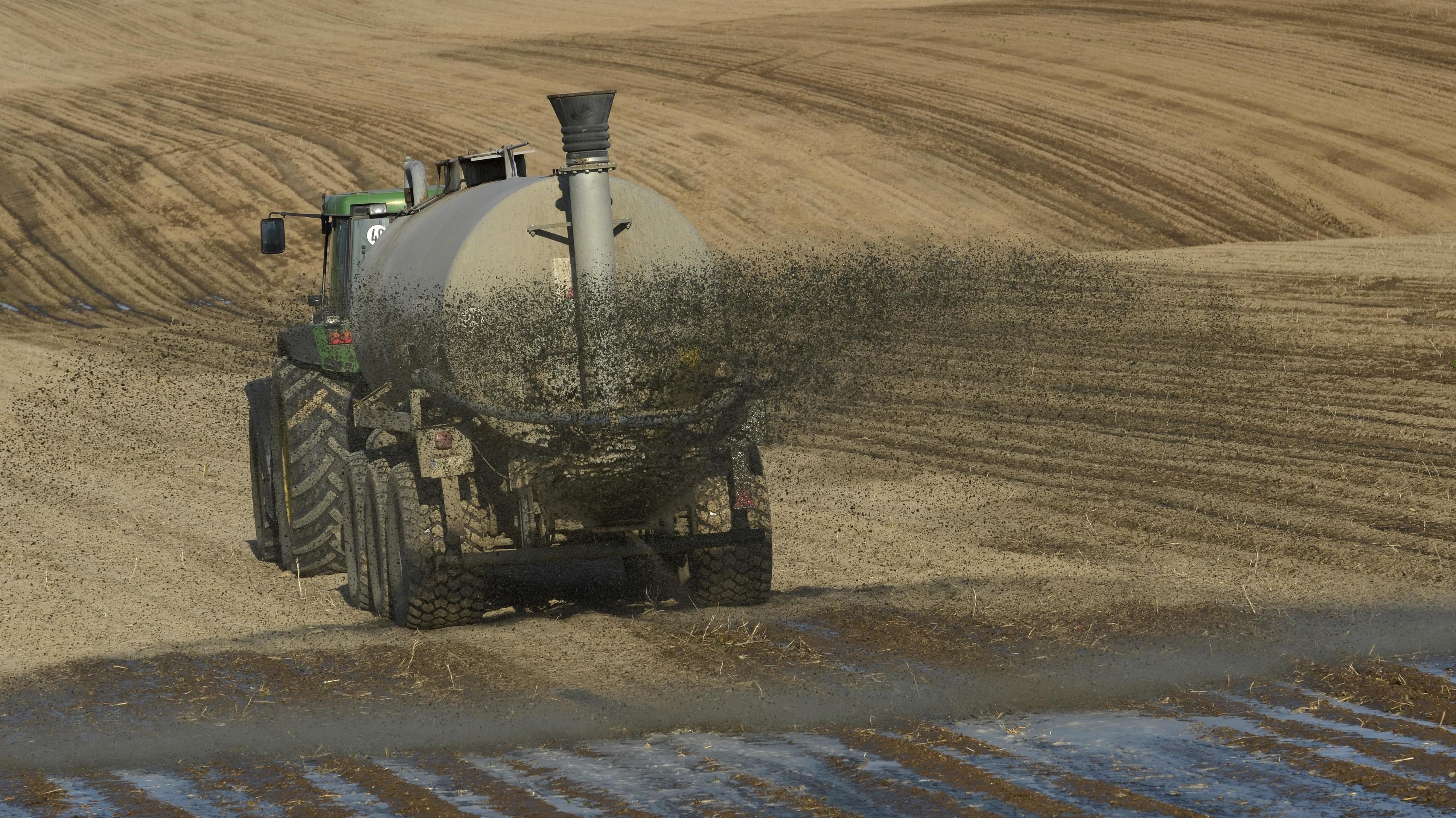 Traktor bringt Gülle auf Feld aus