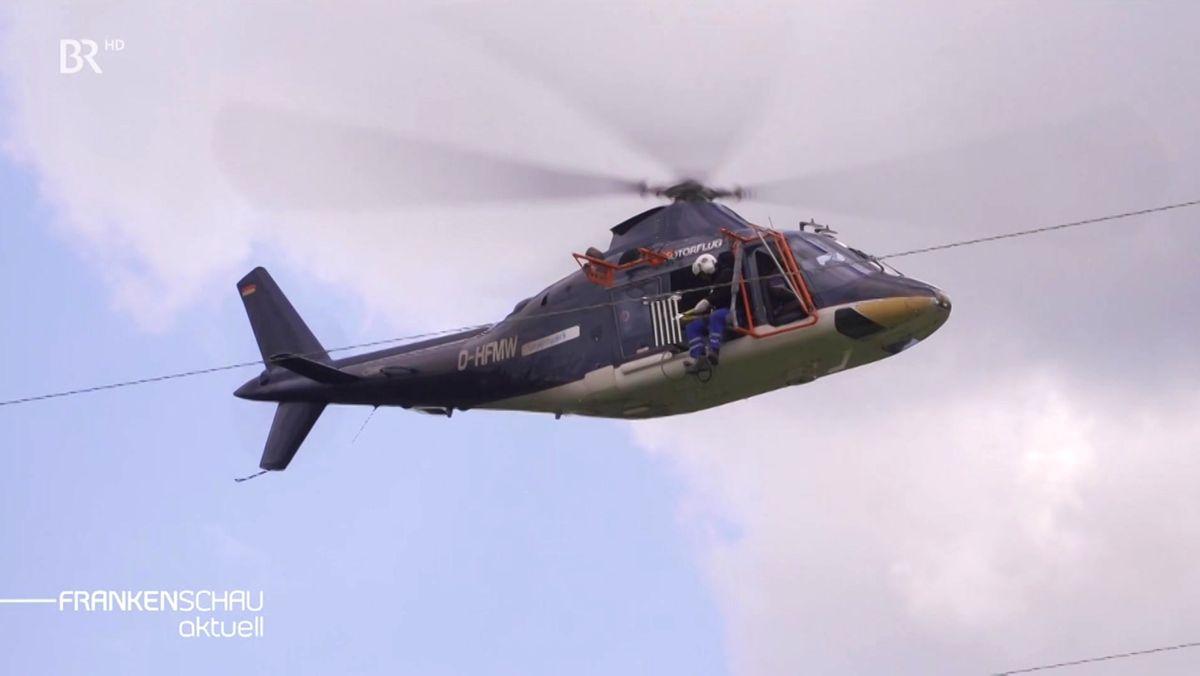 Ein Monteur klemmt vom Hubschrauber aus eine schwarz-weiß gestreifte Vogelwarnfahne an eine Freileitung.