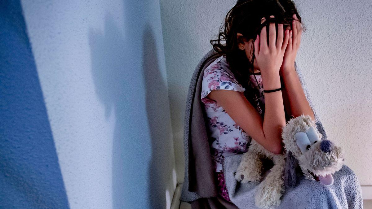 Mädchen sitzt auf dem Boden und hält die Hände vor ihr Gesicht.