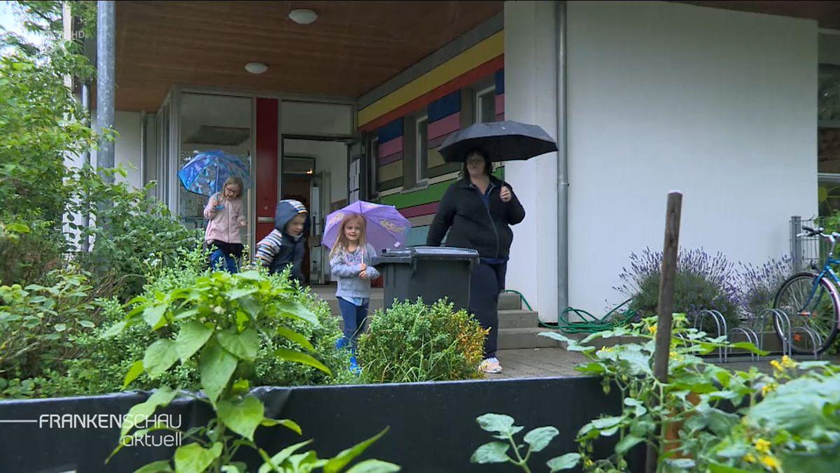 Eine Erwachsene und drei Kinder mit Regenschirmen verlassen ein Haus im Grünen.