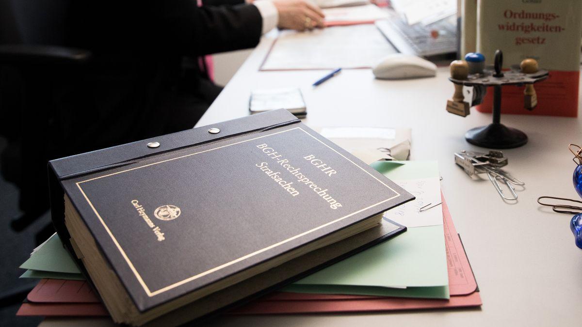 """Die Textsammlung """"BGH-Rechtsprechung Strafsachen"""", Gesetzbücher und Akten sind auf dem Schreibtisch eines Staatsanwalts"""