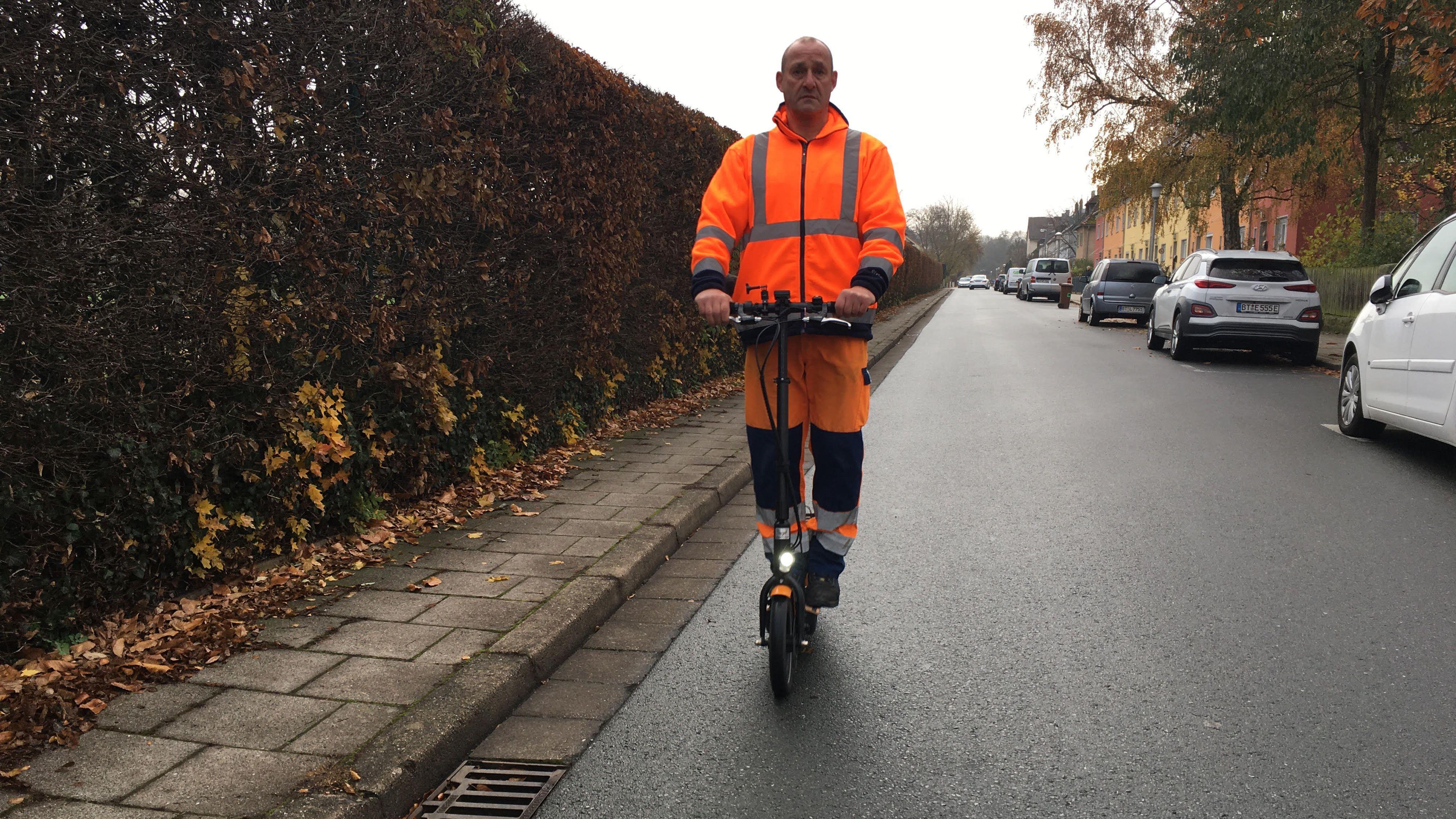 Mitarbeiter der Bayreuther Müllabfuhr fährt in Arbeitskleidung auf seinem E-Roller