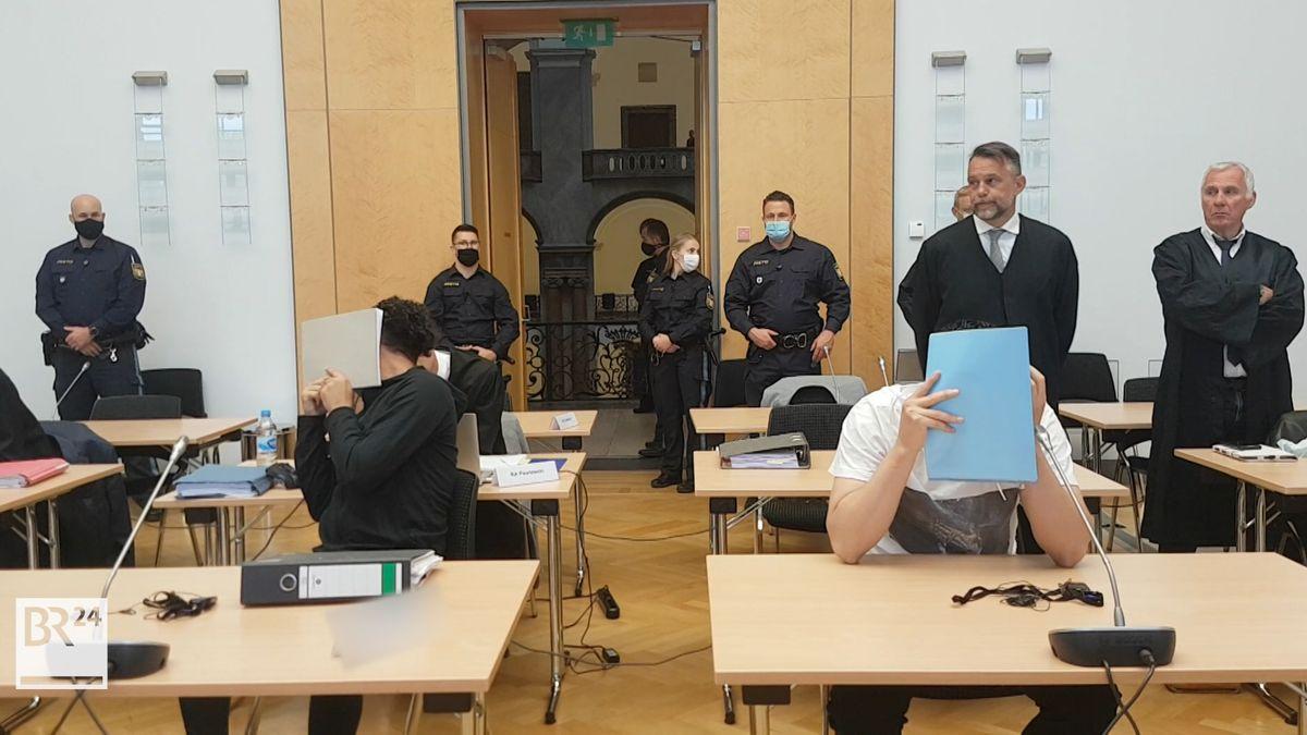 Im Landgericht München sitzen die Angeklagten im Geldautomatensprenger-Prozess an Einzeltischen. Sie verdecken ihre Gesichter. Im Hintergrund stehen Polizeibeamte und Anwälte.