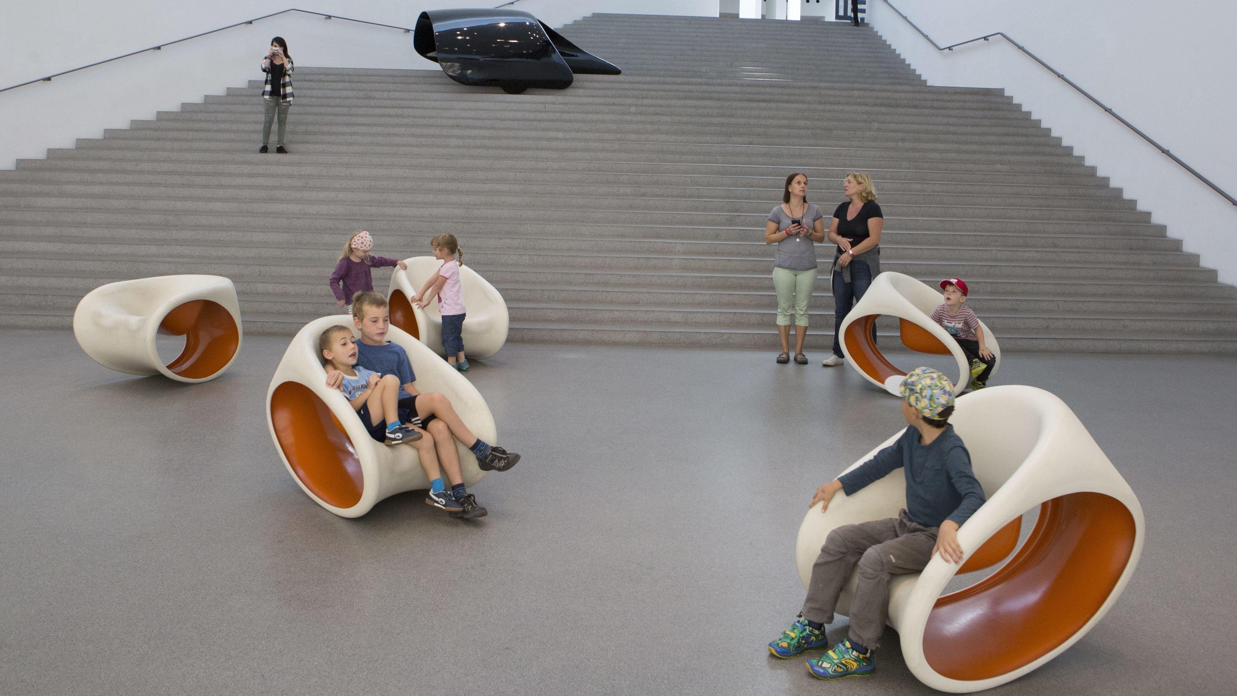 Im Museum Pinakothek der Moderne in München. Luigi Colani und das Teil einer Formstudie für ein flügelartiges Solarmobil (schwarz lackiertes Karbon) und junge Ausstellungsbesucher.