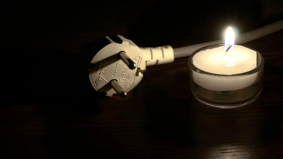 Ein Elektrostecker liegt neben einem brennenden Teelicht