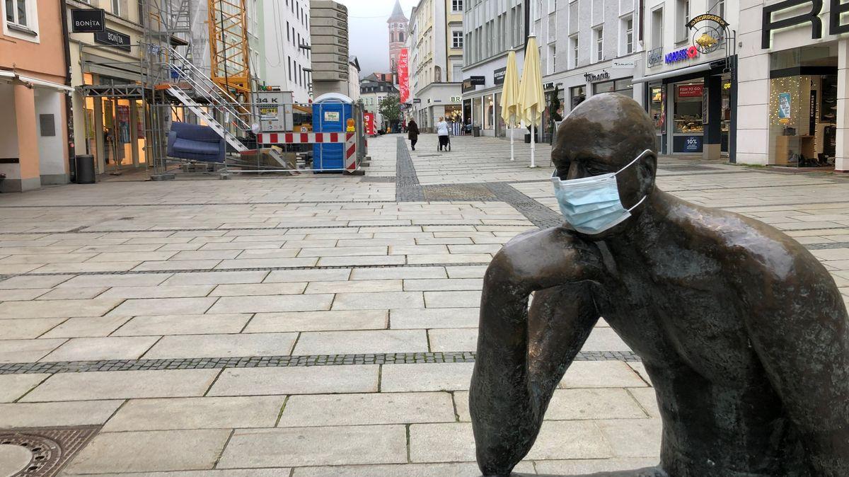 Die Passauer Fußgängerzone ist am Samstagmorgen wie ausgestorben. Eine Statue im Vordergrund trägt eine Gesichtsmaske.