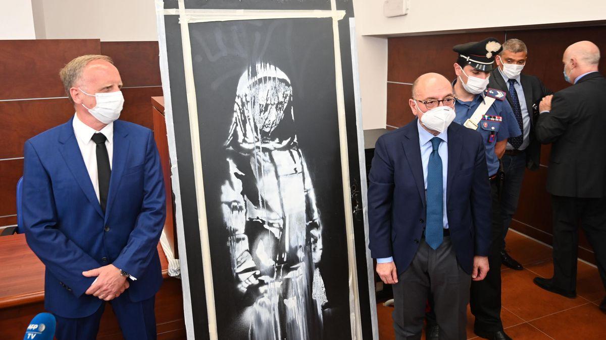Zwei Männer in Anzügen neben dem gestohlenen Banksy-Kunstwerk