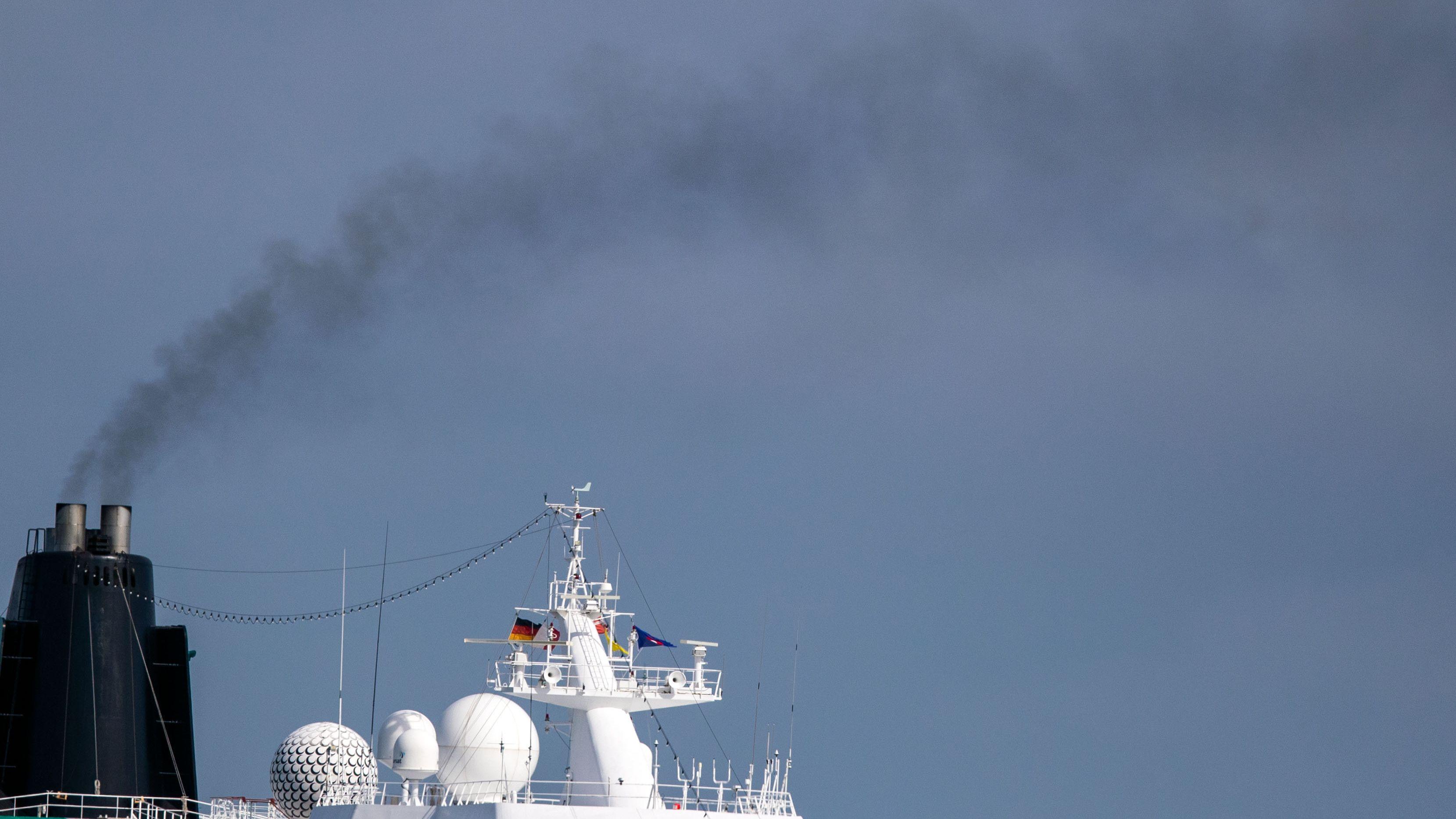Aus dem Schornstein eines Kreuzfahrtschiffes steigt eine dunkle Rauchwolke auf (Symbolbild).