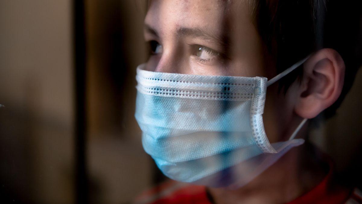 Junge mit Gesichtsmaske hinter einem Fenster.