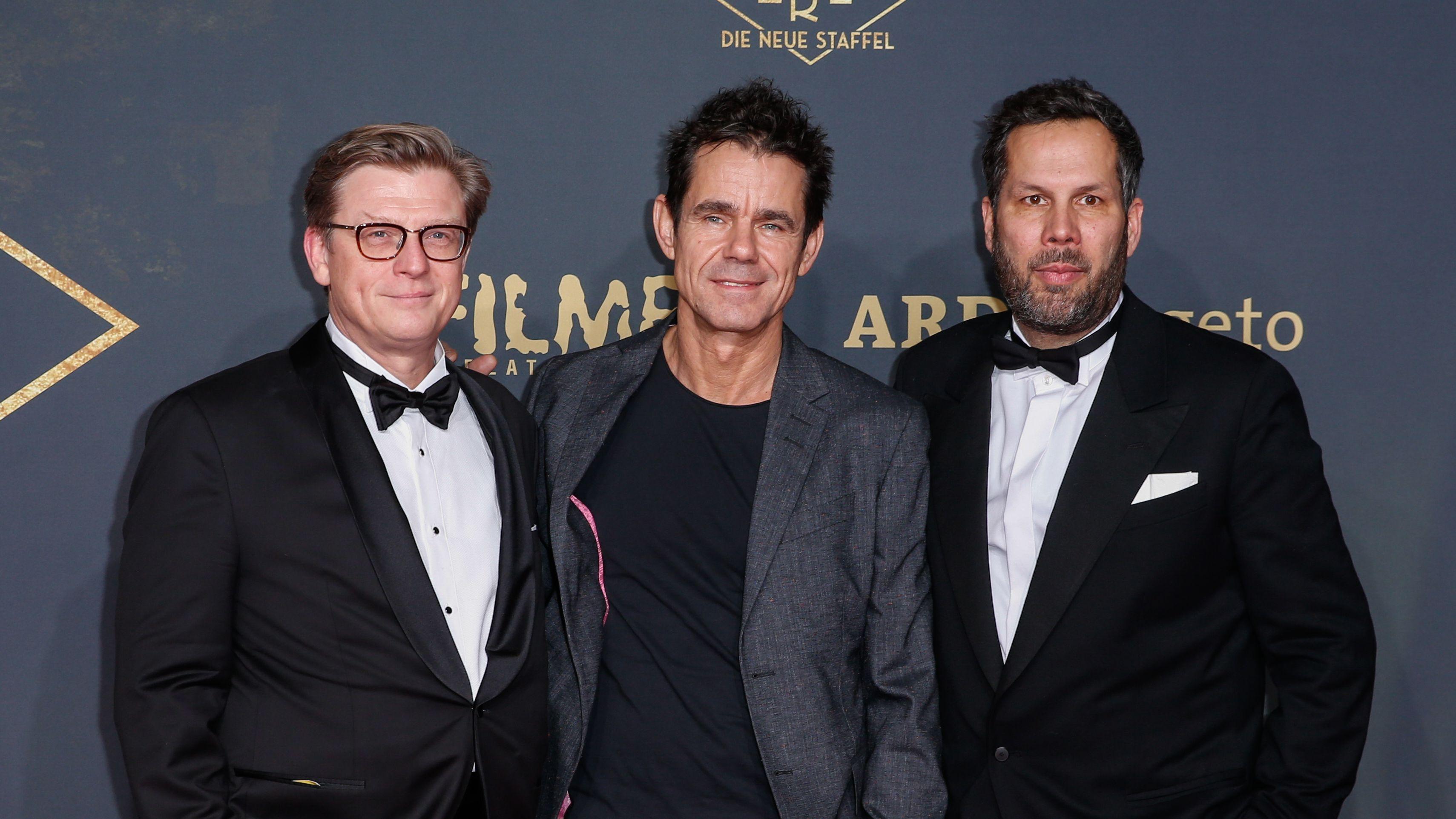 """Achim von Borries, Tom Tykwer und Henk Handloegten stehen bei der Weltpremiere der neuen Staffel von """"Babylon Berlin"""" vor einer Werbewand und lächeln in die Kamera"""