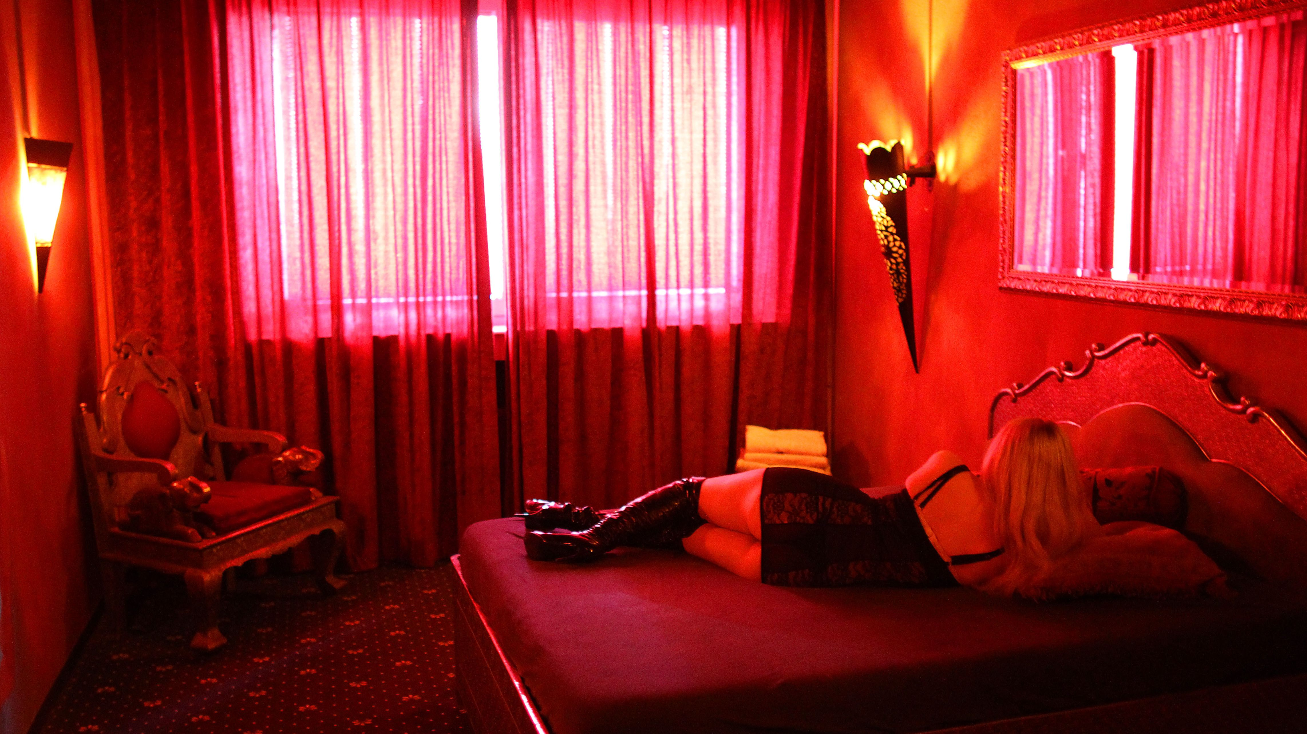 Eine von hinten aufgenommene Prostituierte liegt auf einem Bett in einem rot beleuchteten Raum