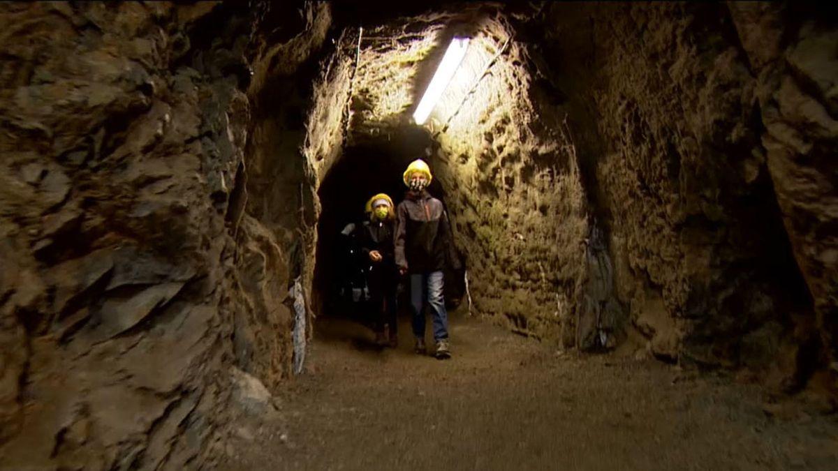 Zwei Besucher des Bergwerks laufen mit Helmen durch einen beleuchteten Stollen.