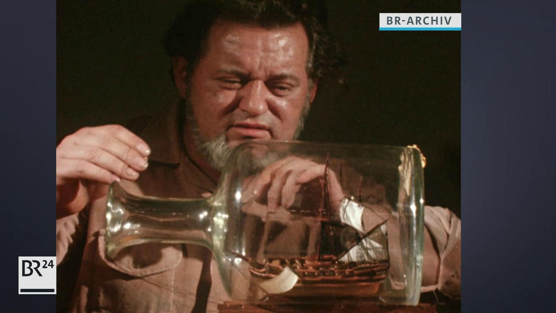 Buddelschiffskapitän Otto Palmen gibt ein Segel in die Flasche
