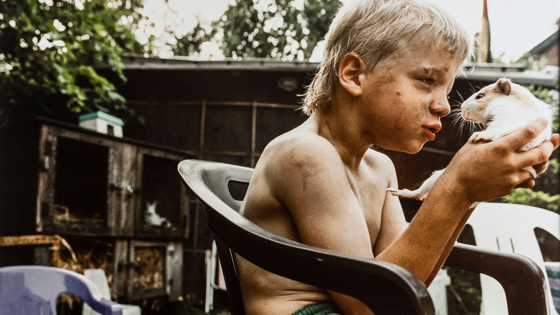 Ein Junge sitzt mit dreckverschmiertem Gesicht und Oberkörper in einem Kleingarten auf einem Plastikstuhl und hält ein Meerschweinchen in der Hand