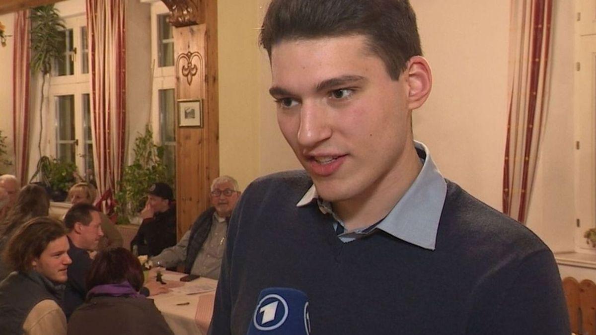 Kristan von Waldenfels, der neue Bürgermeister von Lichtenberg, gibt dem Bayerischen Rundfunk ein Interview, im Hintergrund sitzen seine Parteifreunde an einem Tisch.