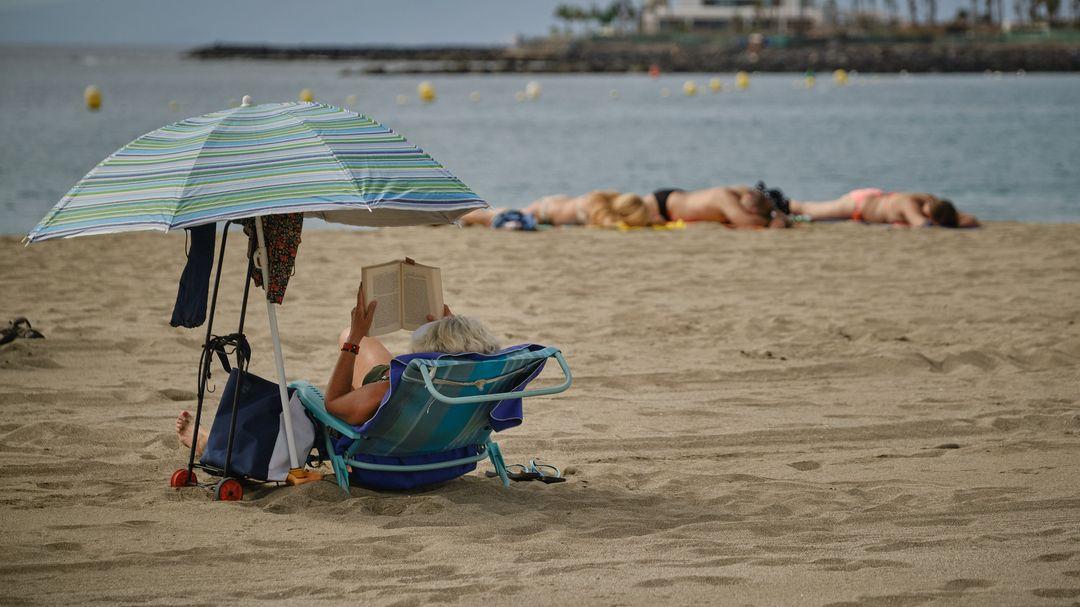 Touristen genießen die Sonne am Strand La Playa de Las Vistas im Süden der Kanaren-Insel