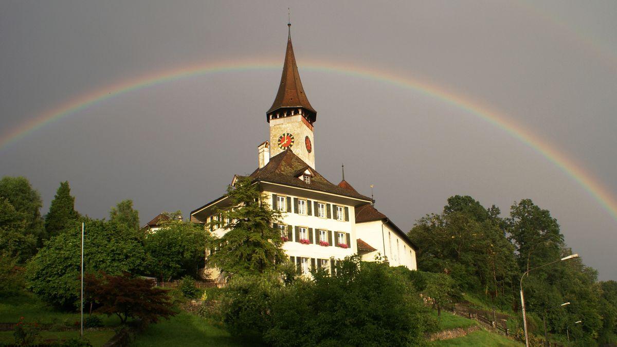Regenbogen hinter Kirchturm über der Gemeinde Hilterfingen am Thunersee.