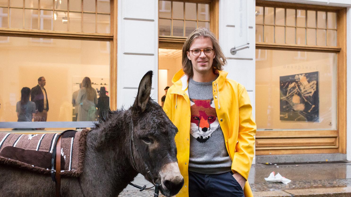 Magnus Resch steht mit einem Esel vor einer Kunstgalerie. Er hat schulterlange braune Haare und trägt eine Hornbrille. Auf seinem grauen Pulli ist ein Fuchs zu sehen, darüber trägt er eine gelbe Regenjacke.