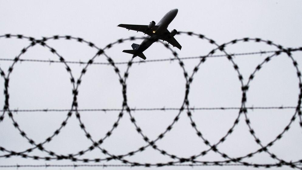 Abschiebung am Flughafen Hannover (Symbolbild): Ein Flugzeug von Lufthansa startet - fotografiert durch Stacheldraht am Flughafenzaun. | Bild:pa/dpa/Julian Stratenschulte