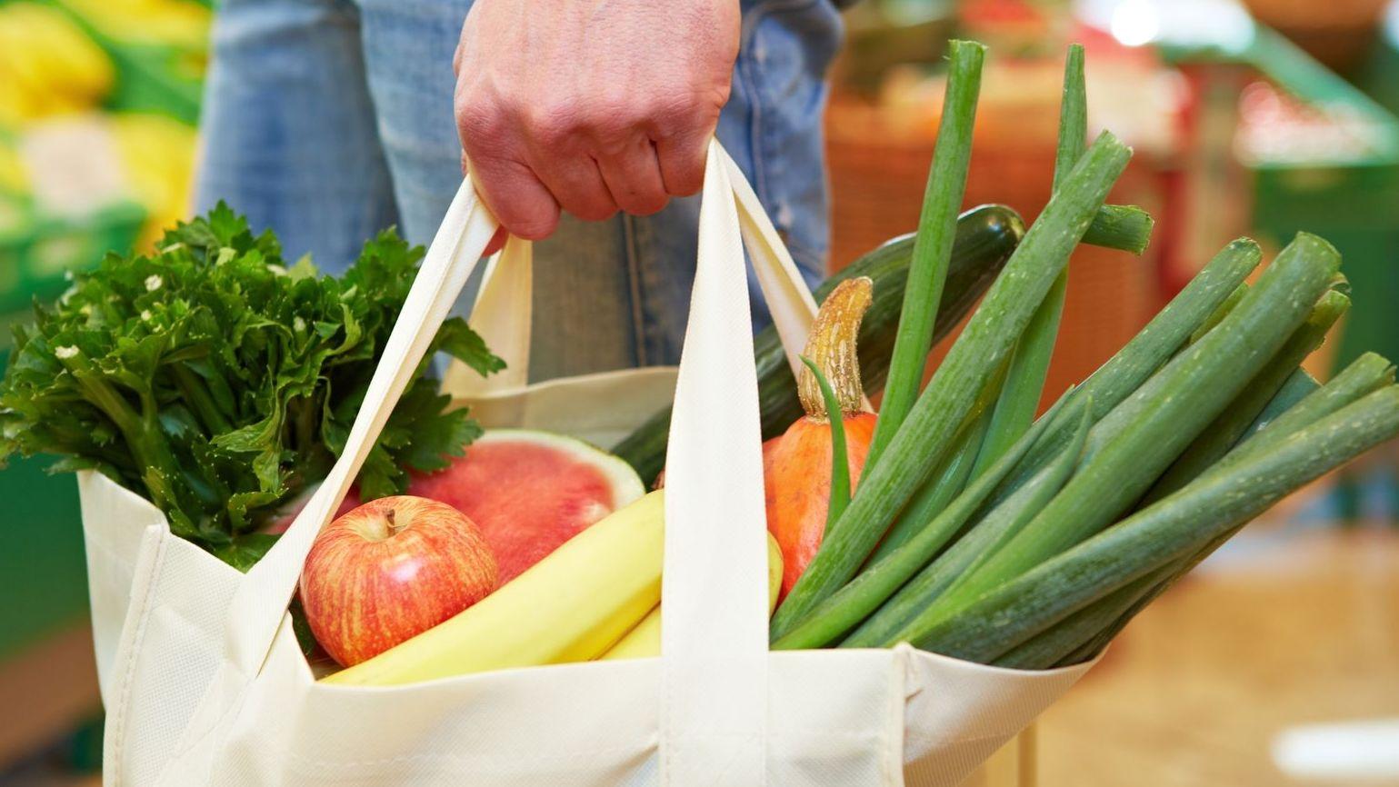 Eine weiße Einkaufstasche aus Stoff mit Äpfel, Bananen, Lauch und einer Gurke.